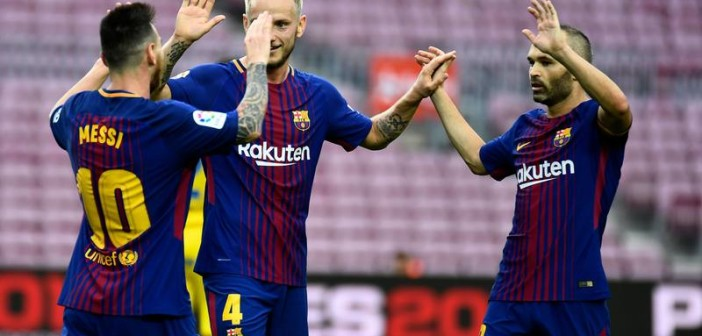 Barcelona's Argentinian forward Lionel Messi (L) celebrates with Barcelona's Croatian midfielder Ivan Rakitic and Barcelona's Spanish midfielder Andres Iniesta after scoring a goal during the Spanish league football match FC Barcelona vs UD Las Palmas at the Camp Nou stadium in Barcelona on October 1, 2017. Barcelona's La Liga match against Las Palmas was played behind closed doors after the Spanish league refused to postpone the match. At least 91 people have been injured in clashes between police and activists in Catalonia over an independence referendum for the region deemed illegal by the Spanish government. / AFP PHOTO / JOSE JORDAN
